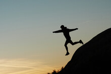 Side View Of Silhouette Of Anonymous Male Athlete Jumping From Hill During Dynamic Training In Highlands At Sunset