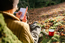 Peaceful Female Traveler Leaning On Tree Trunk And Writing In Diary While Relaxing In Woods During Summer Journey