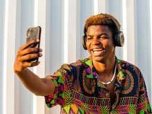 Young Positive African American Male In Headphones And Trendy Clothing Standing On Street And Taking Selfie On Smartphone