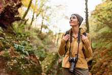 Low Angle Of Traveling Photographer Standing In Woods With Photo Camera And Looking Up While Admiring Nature During Vacation
