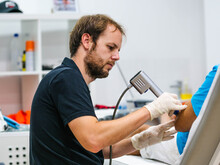 Side View Of Bearded Man In Latex Gloves Using Ultrasound Probe To Heal Elbow Of Crop Patient During Work In Modern Hospital