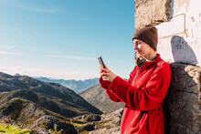 Side View Of Content Hiker Standing In Highland Area And Browsing Mobile Phone While Enjoying Trekking In El Mazuco On Sunny Day