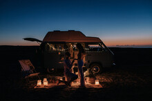 Side View Of Unrecognizable Man Making Proposal For Loving Woman While Standing On Knee Near Illuminated Van At Night