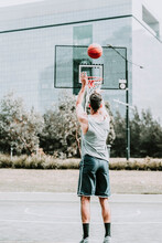 Full Body Back View Of Unrecognizable Determined Young Male Basketball Player In Sportswear Leaping And Shooting Ball Near Hoop While Training Alone On Street Playground