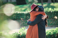 Side View Of Sincere Diverse Female Friends Embracing In Urban Park In Autumn On Sunny Day