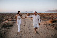 Delighted Couple In White Outfit Holding Hands And Walking Barefoot Along Sandy Road In Savanna At Sunset