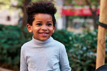 Cheerful Cute African American Child With Curly Hair Standing On Street In Summer And Looking Away