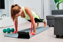 Slim Female In Sportswear Doing Plank Exercise With Resistance Band While Balancing And Watching Video Tutorial On Tablet At Home