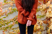 Cropped Back View Of Unrecognizable Lonely Long Haired Brunette In Red Knitted Sweater Standing Against Concrete Wall Covered By Colorful Ivy Plants In Autumn Day