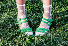 Legs Of Crop Anonymous Female Wearing Green Sandals And Socks With Chamomile Flowers Print While Standing On Lawn In Summer On Sunny Day