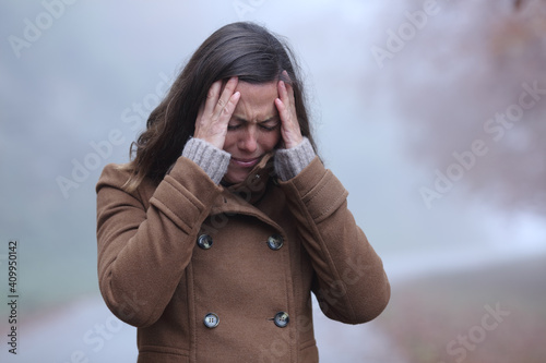Photo Sad woman in winter complaining alone in a park