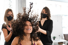Cheerful Satisfied Young Brunette With Long Curly Hair Having Fun And Enjoying New Hairdo In Modern Beauty Salon With Professional Hairdressers