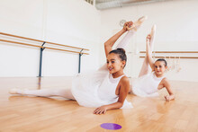 Teenage Ballet Dancers In Tutu And Pointe Shoes Stretching Body During Lesson In Dance Hall Looking Away