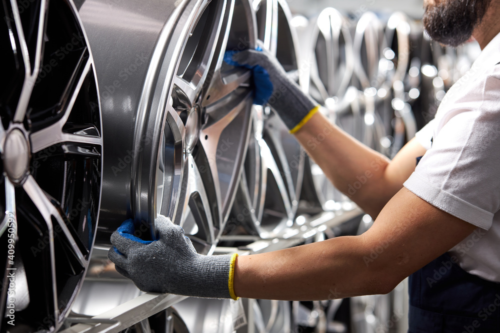 Fototapeta close-up photo of male in gloves taking auto rims from rack, cropped auto mechanic in uniform at work