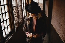 Stylish Female In Elegant Vintage Outfit And Hat Standing In Narrow Hallway Of Old House And Looking At Mirror