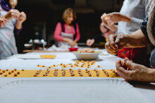 Crop Unrecognizable Housewives Preparing Italian Tortellini From Dough And Raw Meat On Table In Kitchen