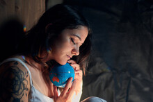 Side View Of Serene Female With Closed Eyes Embracing Earth Globe Showing Concept Of Saving Planet
