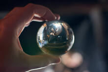 Crop Anonymous Person Looking At Sleeping Woman Relaxing In House Through Glass Ball