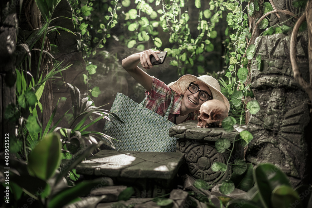 Fototapeta Funny tourist taking a selfie in the jungle with a skull