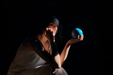 Side View Of Serene Female Holding Earth Globe Showing Concept Of Saving Planet Looking At Camera