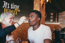 Playful Woman Smearing Nose Of Black Male Friend With Sauce While Sitting In Fast Food Cafe And Having Fun