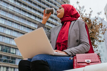 From Below Of Arab Female Entrepreneur In Hijab Sitting On Street With Laptop And Dirking Coffee To Go While Working On Remote Project In City