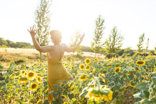 Female In Dress Practicing Yoga In Goddess Pose While Standing With Mudra Hands In Blooming Sunflower Field In Summer