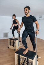 Fit Sportsman And Sportswoman Doing Exercises On Pilates Chair In Bright Gym While Training And Looking Away