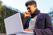 Low Angle Of African American Male Entrepreneur Sitting On Street With Clenched Fist And Closed Eyes While Working On Laptop And Waiting For Approval Of Project