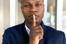 Satisfied African American Male In Casual Outfit Looking At Camera On White Background And Making Silence Gesture