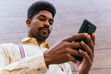From Below Of Serious Bearded African American Businessman In Stylish Casual Shirt Messaging On Smartphone While Standing Against Blurred Wall Of Modern Building