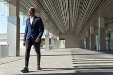 Cheerful Black Male Entrepreneur In Stylish Formal Outfit Walking Along Sunny Street And Looking Away