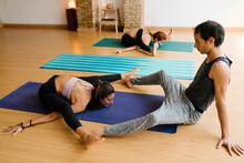 High Angle Of Slim Female Doing Upavista Konasana Pose Near Male Coach And Stretching Body During Group Yoga Lesson In Studio
