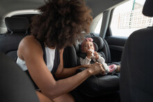 Unrecognizable African American Woman Buckling Up Belt On Car Seat While Looking At Cute Baby