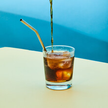 Refreshing Cold Cola Pouring In Glass With Reusable Metal Straw And Ice Cubes Placed On Table In Studio And Showing Zero Waste Concept