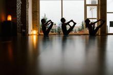 Silhouettes Of Man And Women Doing Upavista Konasana Pose Against Window During Yoga Lesson In Dark Studio