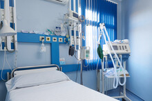 Interior Of Contemporary Hospital Room With Empty Bed And Modern Electronic Medical Equipment