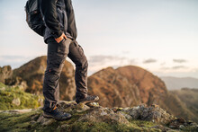 Side View Of Cropped Unrecognizable Lonely Male Explorer With Backpack Standing On Top Of Green Hill And Contemplating Nature While Traveling Through Mountainous Terrain