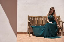 Young Peaceful Female With Long Wavy Hair And In Emerald Elegant Dress Sitting On Wooden Bench In Summer