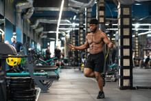 Shirtless Muscular Black Guy Jumping With Skipping Rope In Gym