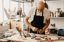 Focused Mature Woodworker Choosing Instruments From Wooden Workbench While Working In Creative Workshop