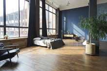 Dark Interior Of A Modern Stylish Huge Open-plan Loft-style Studio Apartment With Columns And High Ceilings. Dark Blue Primed Walls Are Decorated With Wood. Sunlight Enters Through Huge Windows.