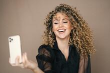 Stylish Cheerful Female Taking Self Portrait On Smartphone On Brown Background In Studio