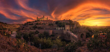 View Across River Of Old City Toledo In Spain With Medieval Castles And Fortresses At Sunset Time With Cloudy Sky And Reflection In River Water