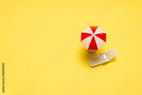 Fotografie, Obraz Two sun loungers and a red umbrella on a yellow background.