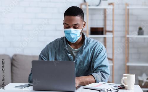 Obraz Black Man Wearing Face Mask Working On Laptop In Office - fototapety do salonu