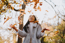 Low Angle Of Carefree Ethnic Female In Warm Coat Tossing Fallen Autumn Leaves In Park On Sunny Day While Having Fun And Looking Up