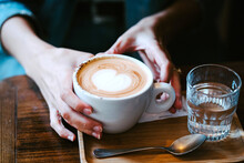 Crop Anonymous Female Holding Cup Of Fresh Hot Aromatic Coffee And Glass Of Water In Cafe