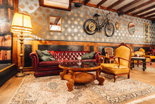 Comfortable Vintage Interior Of Spacious Hall Of Restaurant With Stylish Armchairs And Sofa Under Crystal Chandeliers