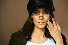 Modern Young Female Model In Stylish Black Leather Cap And Trendy Round Glasses Looking At Camera Against Brown Background